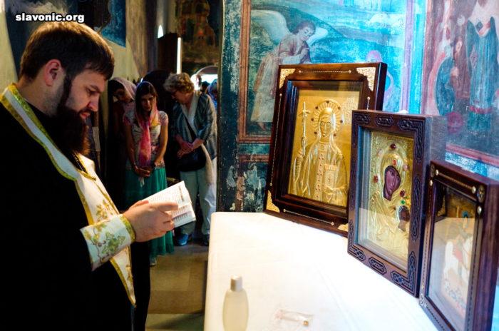 Архимандрит Александр (Беля) освящает иконы на мощах святой Нины